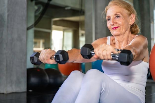 Senior mujer caucásica brazo de entrenamiento con mancuernas en el gimnasio.