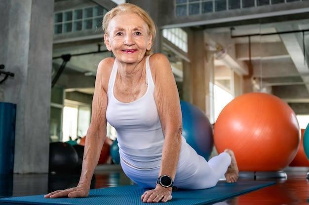Senior mujer caucásica haciendo ejercicio de yoga en el gimnasio.