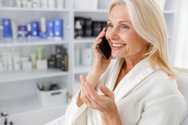 Senior mujer caucásica sonriendo en bata de baño blanca, hablando por teléfono móvil en el salón de esteticista.