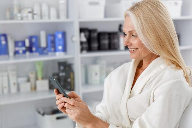 Senior mujer caucásica sonriendo en bata de baño blanca, sosteniendo el teléfono móvil en el salón de esteticista.