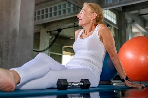 Senior mujer caucásica sonriendo y feliz en el gimnasio.