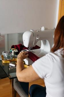 Senior mujer cosiendo mascarillas de tela para familiares y amigos
