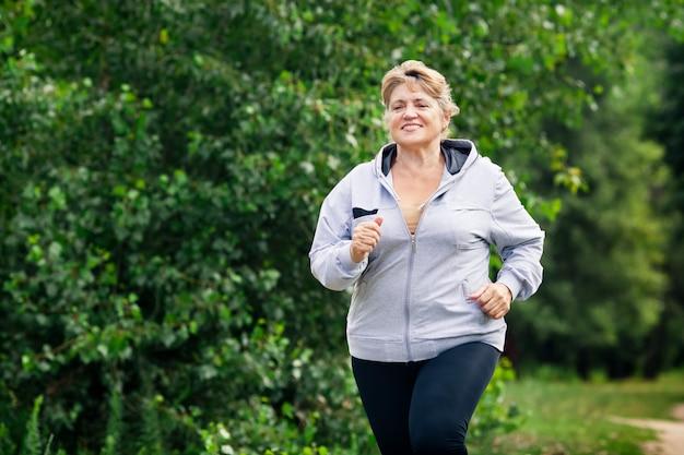 Senior mujer deportiva corre en el parque en la pista