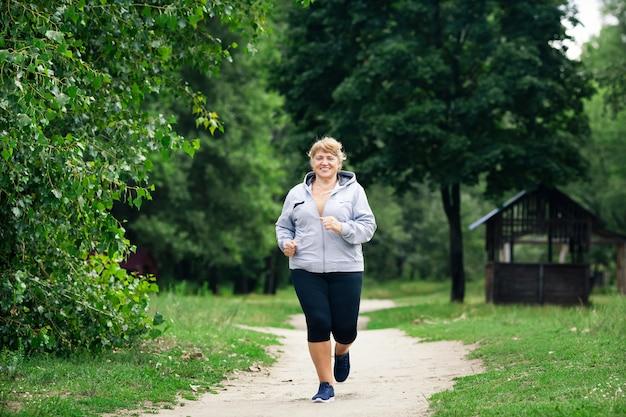 Senior mujer deportiva corriendo en el parque en la pista