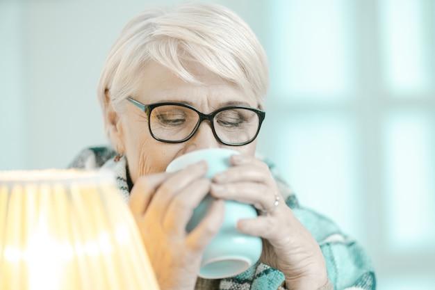 Senior mujer envuelta en una tela escocesa a cuadros está bebiendo té en casa