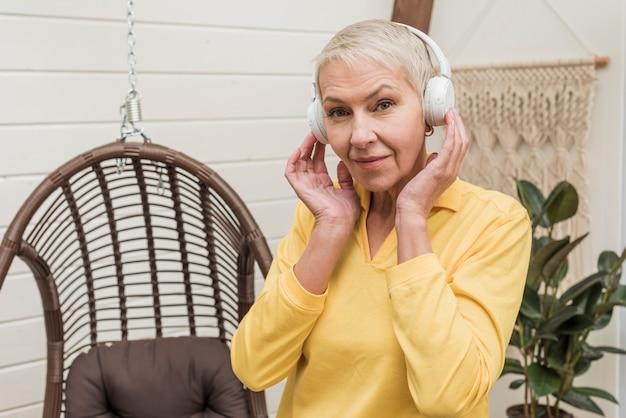 Senior mujer escuchando música aunque auriculares blancos