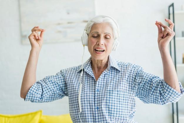 Senior mujer escuchando música en auriculares chasquear los dedos