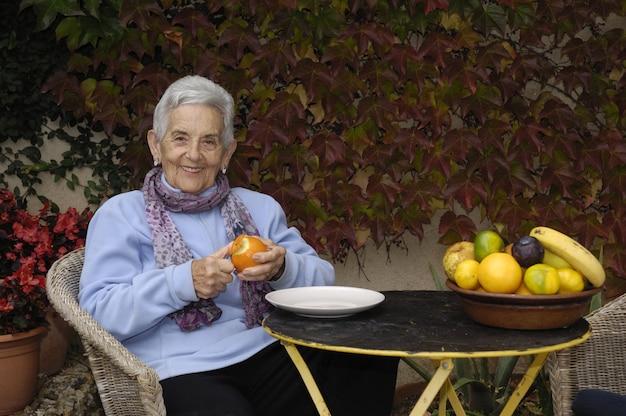Senior mujer con una fruta naranja
