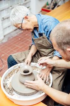 Senior mujer girando arcilla sobre una rueda con el maestro en la clase de cerámica
