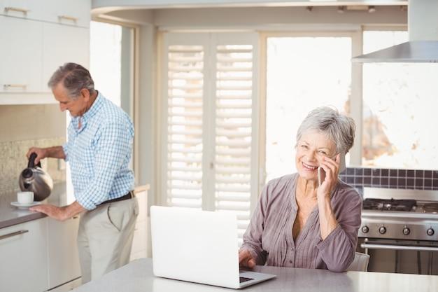 Senior mujer hablando por teléfono móvil con marido haciendo té en segundo plano.