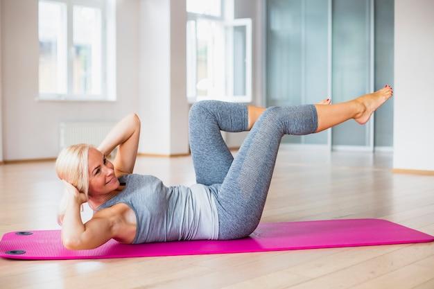 Senior mujer haciendo abdominales en estera de yoga