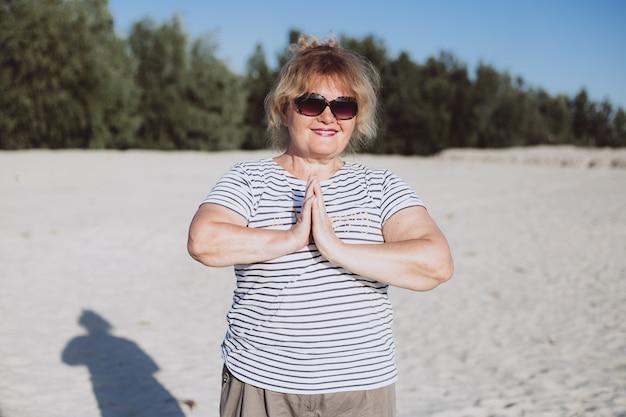 Senior mujer haciendo ejercicios de yoga en la playa en arena