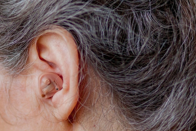 Senior mujer insertando audífono en sus oídos
