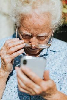 Senior mujer leyendo desde un teléfono móvil