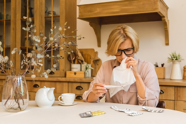 Senior mujer madura con píldoras que miden la temperatura corporal con termómetro médico en la cocina de casa. resfriado y gripe, concepto de coronavirus covid-19.