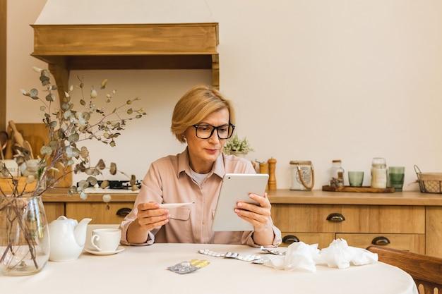 Senior mujer madura con píldoras que miden la temperatura corporal con termómetro médico en la cocina de casa. resfriado y gripe, coronavirus covid-19. usando tableta.