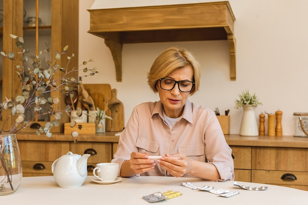 Senior mujer madura con píldoras que miden la temperatura corporal con termómetro médico en la cocina de casa. resfriado y gripe, coronavirus covid-19.