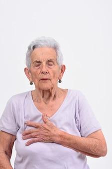 Senior mujer con la mano en el corazón por un susto