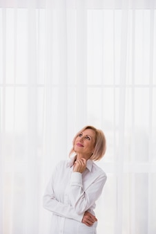 Senior mujer mirando hacia arriba con espacio de copia