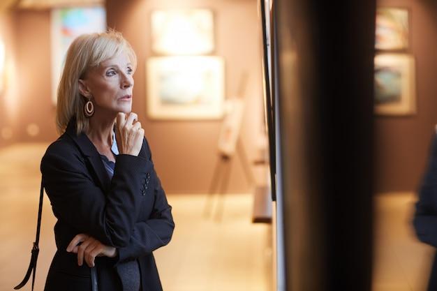 Senior mujer mirando pinturas en la galería de arte
