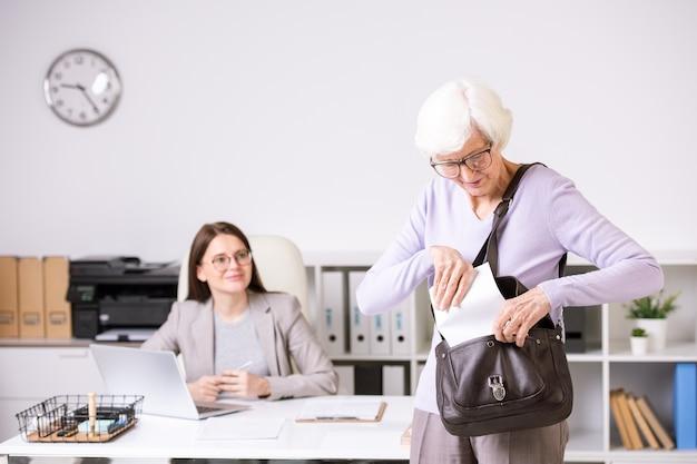 Senior mujer de pelo blanco con gafas poniendo papel en la bolsa mientras sale del centro de trabajo social