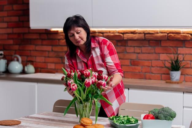 Senior mujer pone las flores en orden antes de cenar en la cocina