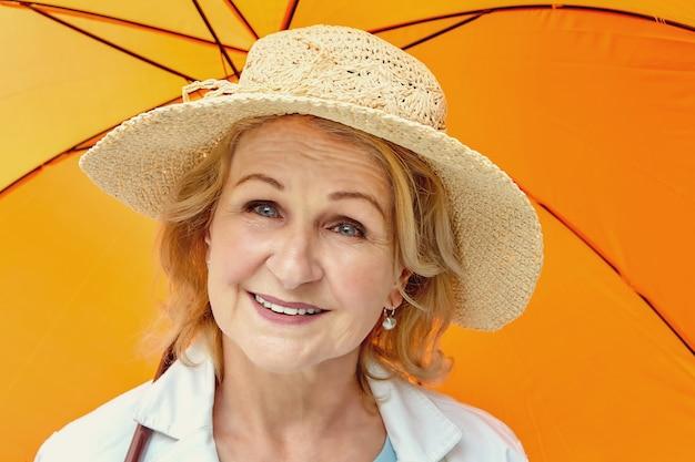 Senior mujer rubia atractiva blanca de unos 62 años con sombrero está de pie bajo el paraguas naranja durante el día.