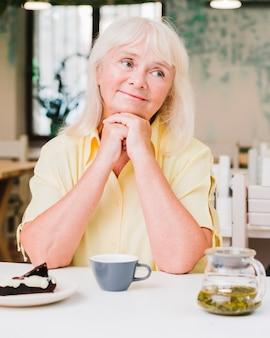 Senior mujer sentada en la cocina con taza y pastel