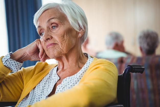 Senior mujer en silla de ruedas parece preocupada