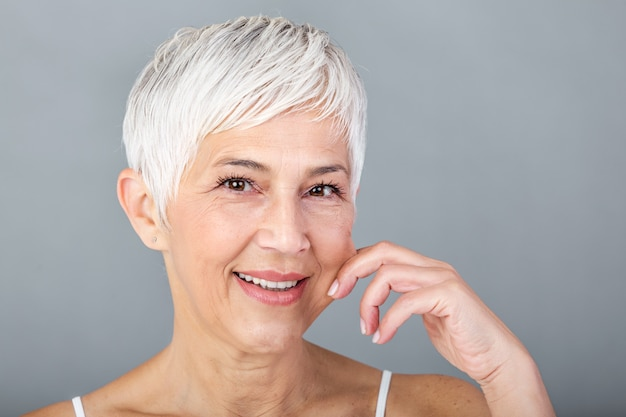 Senior mujer tirando de las mejillas para sentir suavidad y mirando a cámara. retrato de la belleza de la mujer madura feliz que sonríe con las manos en la mejilla aislada sobre fondo gris. proceso de envejecimiento y concepto de piel.