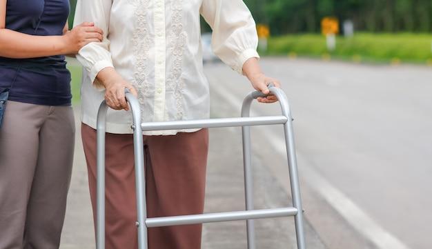 Senior mujer usando un andador cruzar la calle con el cuidador