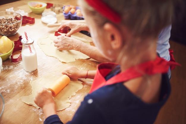Senior con niña horneando galletas en navidad