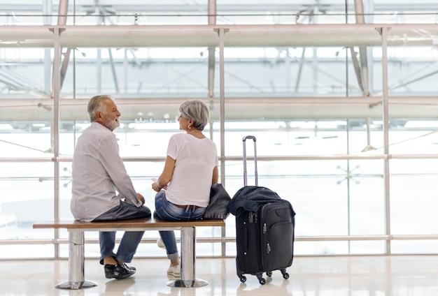 Senior par esperando embarque dentro del aeropuerto