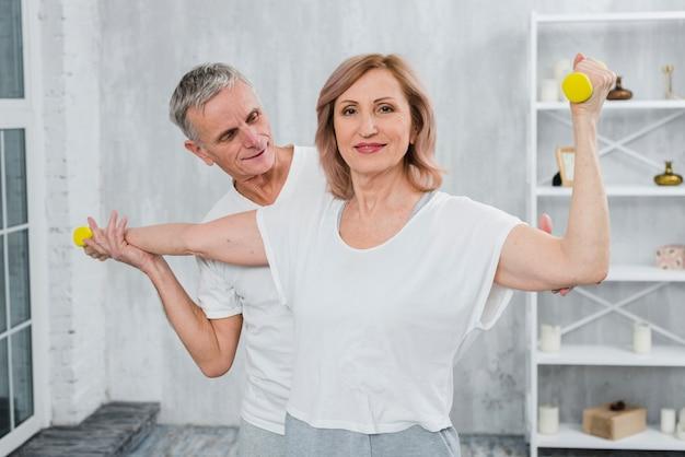 Senior par hacer ejercicio juntos en casa con pesas