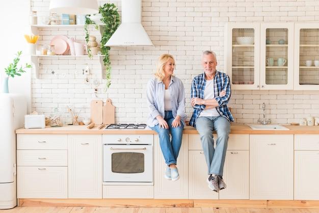 Senior par sentado en el mostrador de la cocina