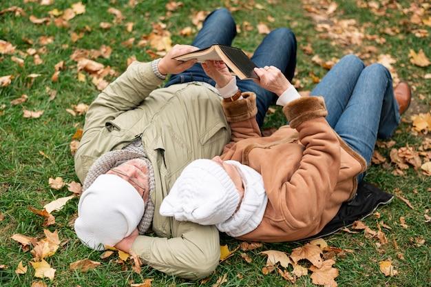 Senior par tiempo para leer mientras está sentado en el campo con hojas