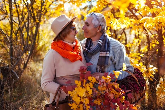 Senior pareja abrazándose en el bosque de otoño y relajarse al aire libre