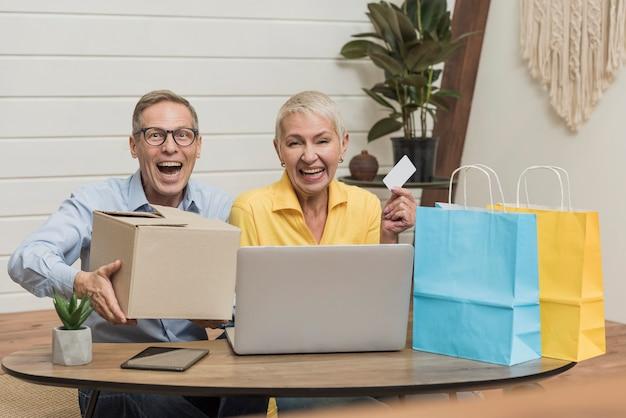 Senior pareja abriendo sus bolsas y cajas de compras