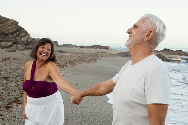 Senior pareja amorosa pasar tiempo juntos en la playa.