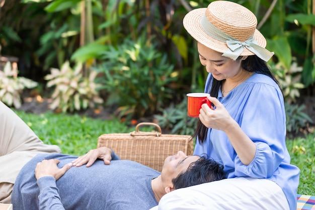 Senior pareja asiática bebiendo café y picnic en el jardín.