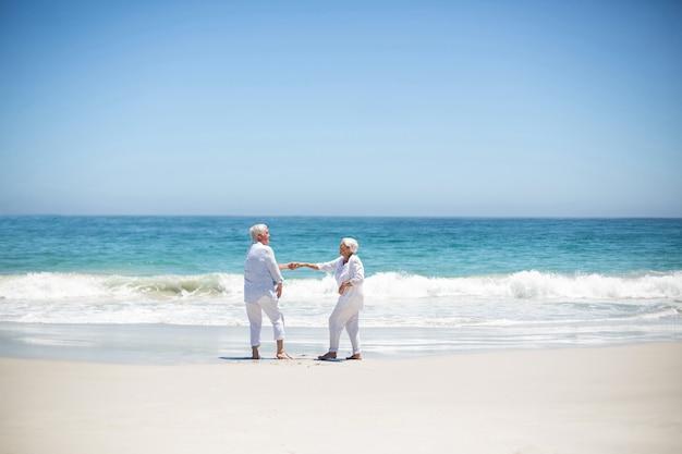 Senior pareja bailando en la playa