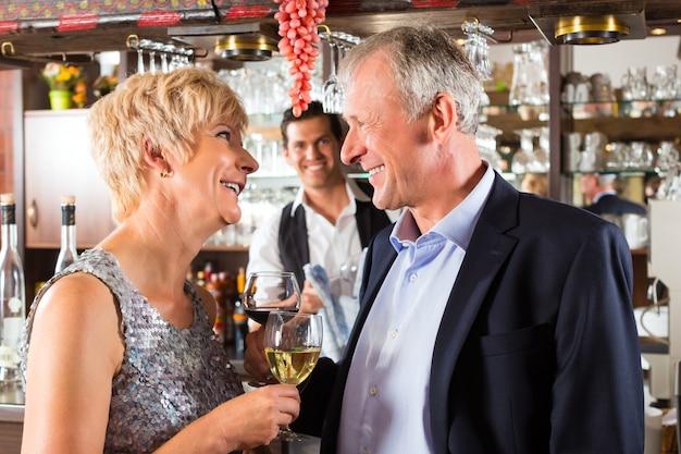 Senior pareja en el bar con una copa de vino en la mano