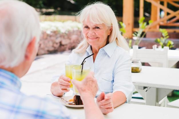 Senior pareja bebiendo jugo de naranja en la terraza al aire libre