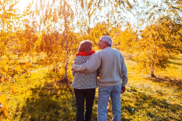 Senior pareja caminando en el bosque de otoño hombre de mediana edad y mujer abrazando