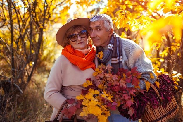 Senior pareja caminando en el bosque de otoño.