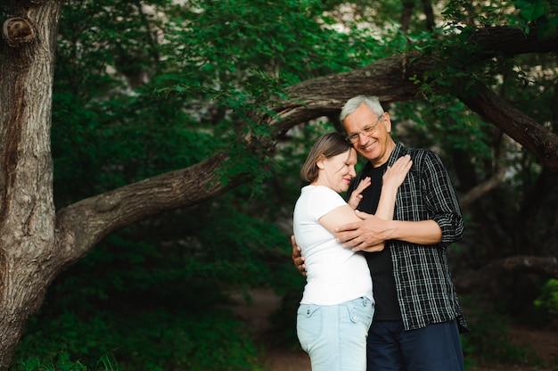 Senior pareja caminando juntos en un bosque, primer plano.