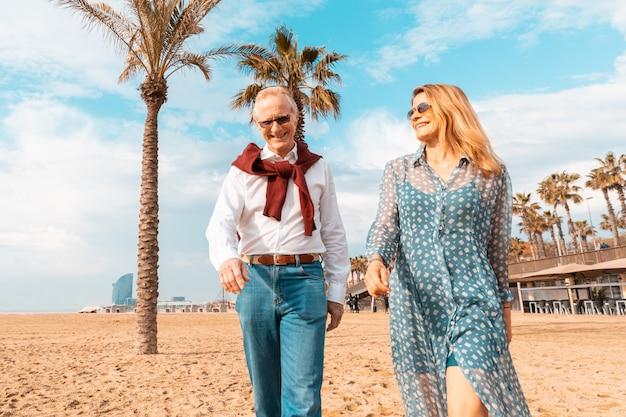 Senior pareja caminando por la playa en barcelona