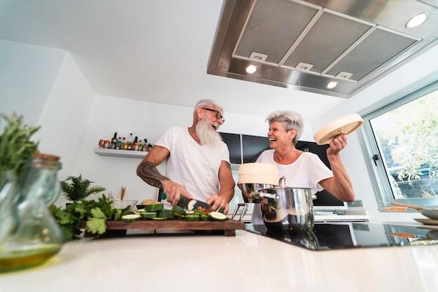 Senior pareja cocinando en casa mientras prepara el almuerzo vegetariano