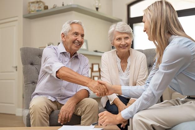 Senior pareja dándose la mano con el asesor financiero