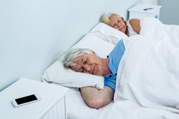 Senior pareja descansando en la cama con el teléfono en la mesa